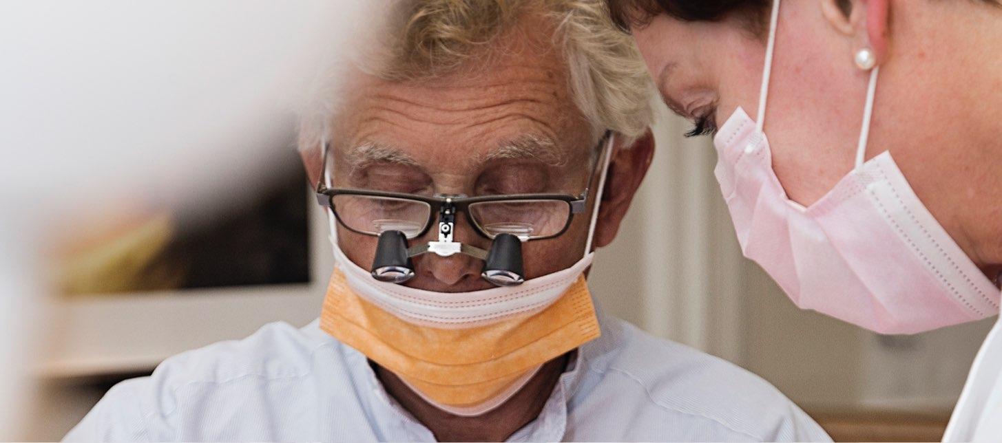 närbild på tandläkare werner med munskydd och förstoringsglasögon